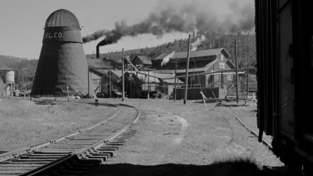 MS Shot of lumber mill with smoke coming from furnace with railroad tracks