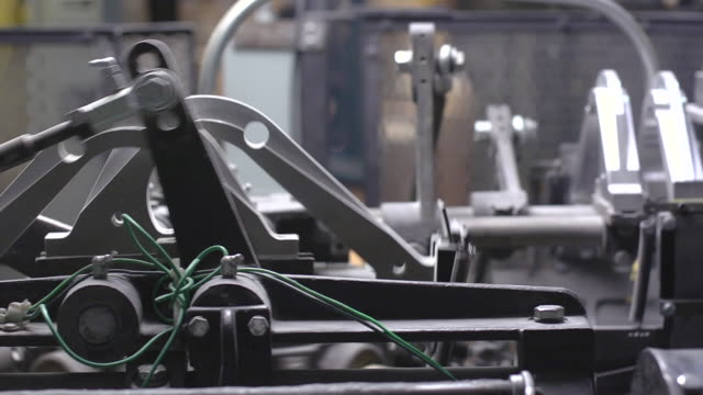 ms pan shot of machine arms moving / chelsea, michigan, united states - metall stock-videos und b-roll-filmmaterial