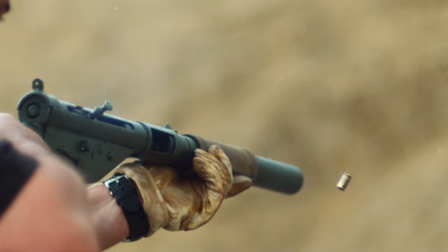 CU SLO MO Shot of machine gun being fired / United Kingdom