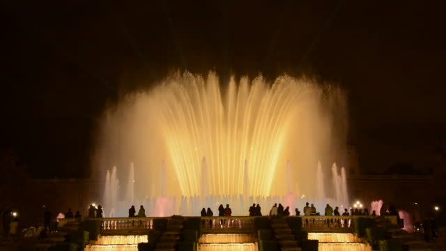 MS Shot of Magic Fountain with people in Barcelona illuminated at night / Barcelona, Catalunya, Spain