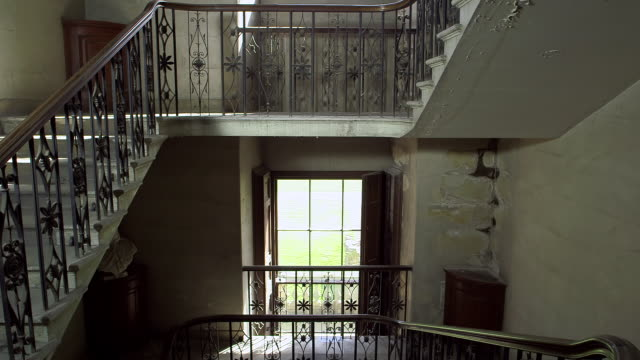 MS Shot of maid carries water up staircase / United Kingdom