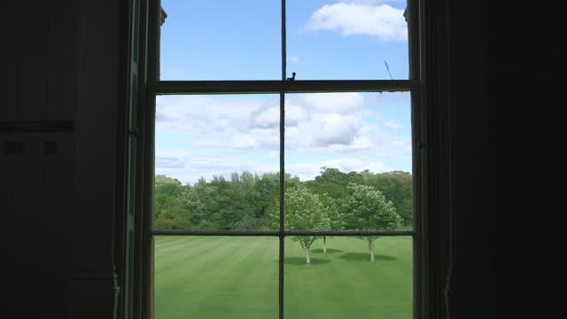 MS Shot of maid opening window shutters / United Kingdom