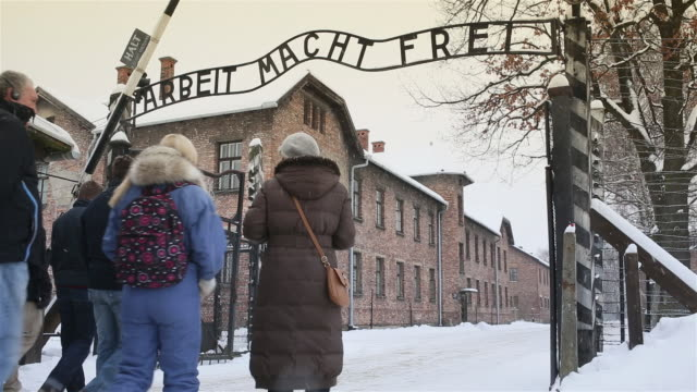 ms shot of main entrance gate at auschwitz with tourists walking through frame with snow rain / auschwitz-birkenau, krakow, poland - konzentrationslager stock-videos und b-roll-filmmaterial