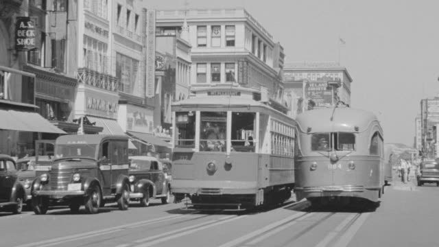 ms shot of main street with buildings on both sides and vehicle traffic on road including trolleys - tram stock videos & royalty-free footage