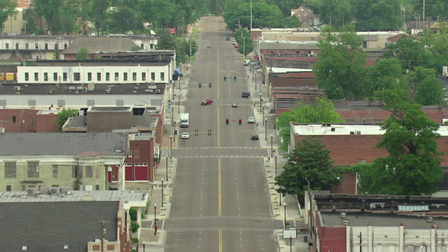 MS AERIAL Shot of main street with cars driving and building roof tops / Greenville, Mississippi, United States