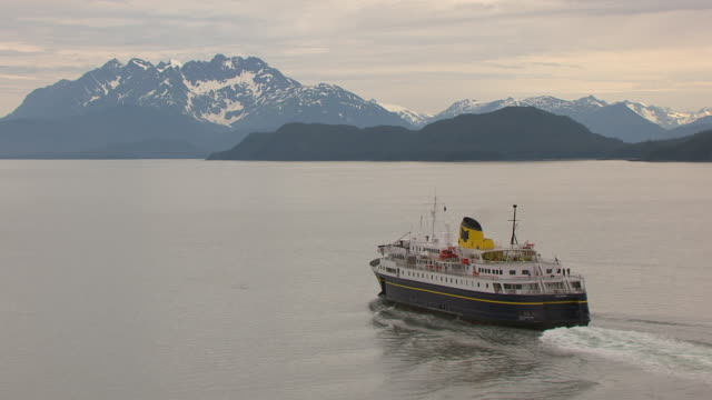 MS AERIAL Shot of Malaspina ferry in Favorite Channel with dolphins swimming alongside ferry / Alaska, United States