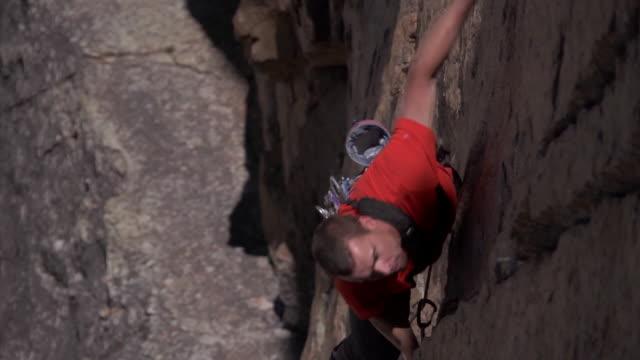 vidéos et rushes de ms zo shot of male climber climbing rock with man is in sun shade line / estes park, colorado, united states - un seul homme d'âge moyen