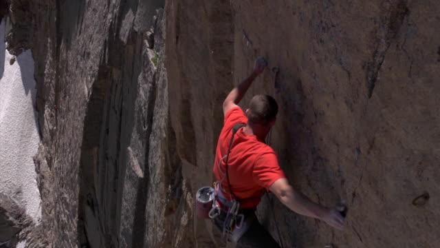vidéos et rushes de ms zo zi shot of male climber climbing very difficult rock and falling with snow in backdrop / estes park, colorado, united states - un seul homme d'âge moyen