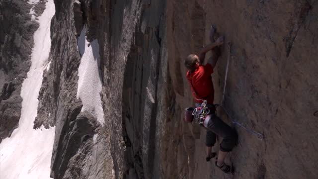 vidéos et rushes de ms slo mo shot of male climber climbing very difficult rock with snow in backdrop / estes park, colorado, united states - un seul homme d'âge moyen