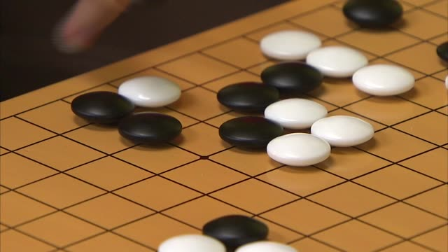 Shot of Male hand Placing a Black stone on GO board(Go is Popular Korean board Game, It is also called Weiqi in Chinese, Igo in Japanese, and Baduk in Korean)