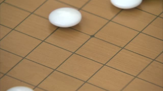 Shot of Male hand Placing a White stone on GO board(Go is Popular Korean board Game, It is also called Weiqi in Chinese, Igo in Japanese, and Baduk in Korean)