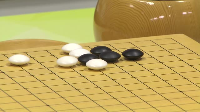 Shot of Male hand placing Black and Whtie stone one by one on Go board(Go is Popular Korean board Game, It is also called Weiqi in Chinese, Igo in Japanese, and Baduk in Korean)