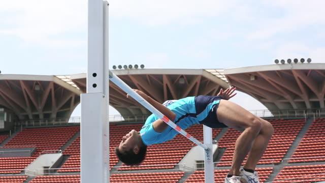vidéos et rushes de ms la shot of male high jumper clearing bar / tokyo, japan - poteau d'appui
