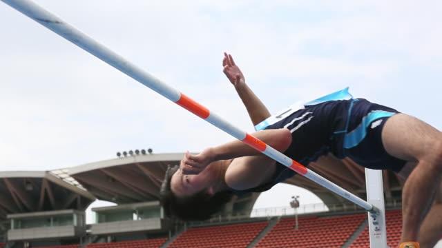 vidéos et rushes de cu la shot of male high jumper clearing bar / tokyo, japan - poteau d'appui