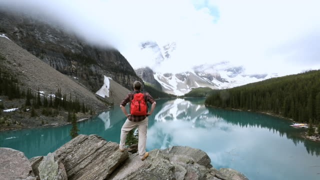 ws shot of male hiker moraine lake valley alberta / canada - valley of the ten peaks stock videos and b-roll footage