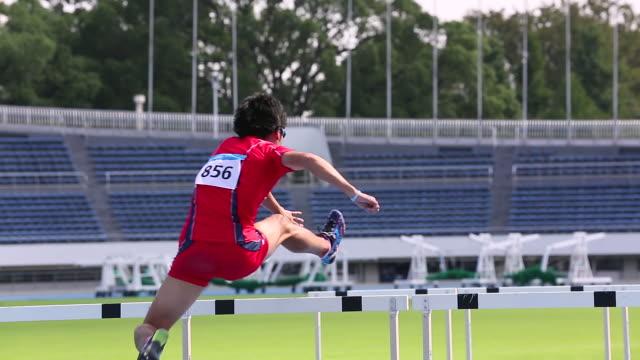 ms shot of male runner jumping hurdles / tokyo, japan - 陸上選手点の映像素材/bロール