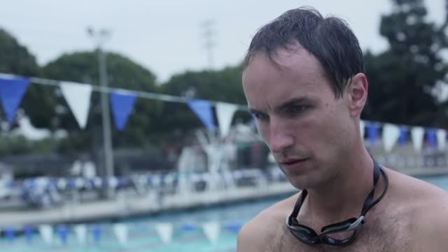 vídeos de stock, filmes e b-roll de cu shot of male swimmer puts on swim cap / los angeles, california, united states  - touca de natação