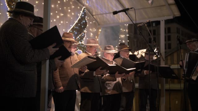 shot of male voice choir on rathausplatz at christmas, vienna, austria, europe - 賛美歌点の映像素材/bロール