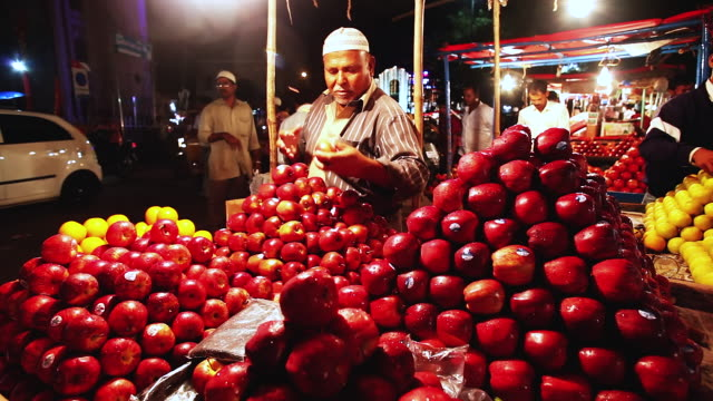 MS Shot of man arranging apples on fruit stall / Hyderabad, Andhra Pradesh, India
