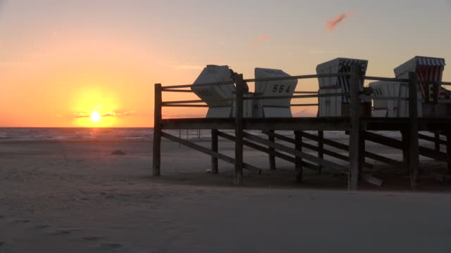 ws shot of man arranging roofed wicker chair along beach side during sunset, north sea north frisia, / st. peter ording, schleswig holstein, germany - north sea stock videos & royalty-free footage