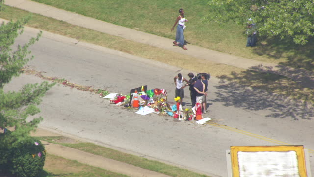 MS AERIAL Shot of man being interviewed by television crew at street memorial where Michael Brown was killed on Canfield Driver in Ferguson / St Louis, Missouri, United States
