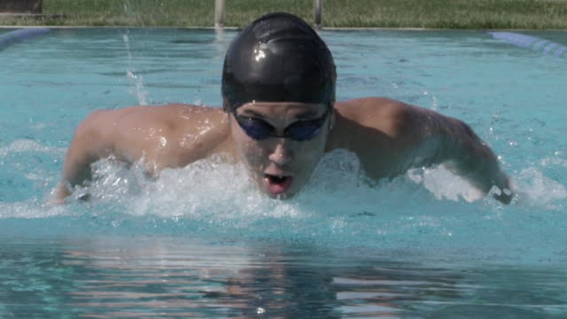 cu slo mo shot of man black swim cap, swimming butterfly stroke / davis, california, united states  - swimming cap stock videos & royalty-free footage