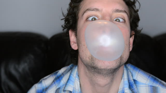cu shot of man blowing chewing gum bubble until it bursts / london, greater london, united kingdom - bubble gum stock videos & royalty-free footage