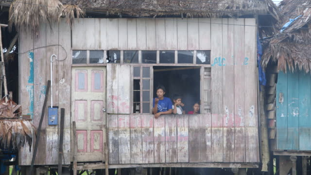 ms shot of man boy and woman stand by window of stilt house / iquitos, maynas, peru - stilt house stock videos & royalty-free footage