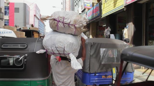 ms pov shot of man carrying heavy load through busy streets of pettah market / colombo, western province, sri lanka - sri lanka people stock videos & royalty-free footage