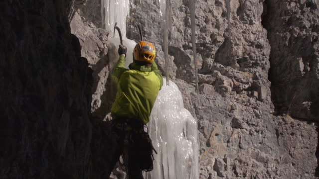 ms pan shot of man climbing up thin strip of ice and he is in sun or shadow line / ouray, colorado, united states - 崖点の映像素材/bロール