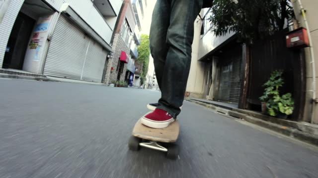 vídeos y material grabado en eventos de stock de ms ts shot of man cruising on skateboard / chiyoda ku, tokyo, japan - pasear en coche sin destino