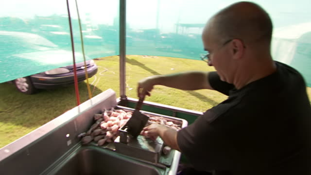 stockvideo's en b-roll-footage met ms shot of man cutting up frog legs at food stand during rayne frog festival / rayne, louisiana, united states - alleen één oudere man