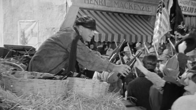 ms pan shot of man distributing wine bottle at market place and soldiers marching - military parade stock videos and b-roll footage
