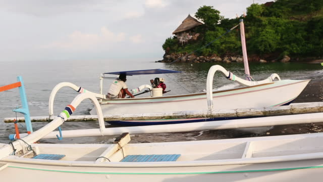 ms pan shot of man docking his boat onto beach / ubud, bali, indonesia - ubud district stock videos & royalty-free footage