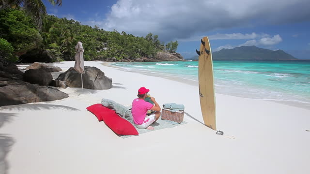 ws shot of man drinking soda on beach / north island, seychelles - seychelles stock videos & royalty-free footage