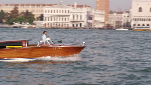 ms ts shot of man driving boat in river/ venice, italy - traghetto video stock e b–roll