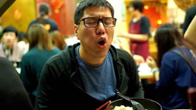 2 Shot of Man Eating Hot Hong Kong Wonton or Dumpling from Chinese restaurant