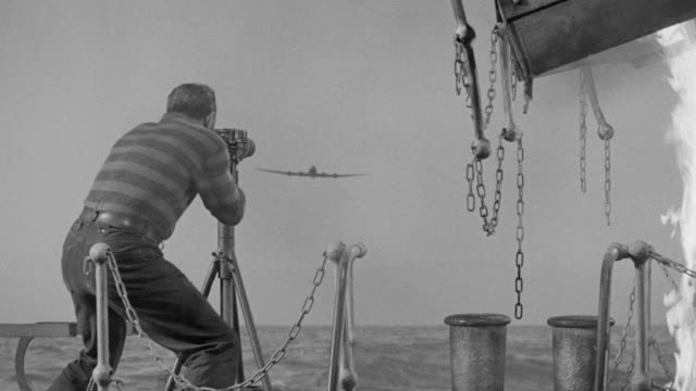 ms shot of man firing on plane from ship - warner bros stock videos and b-roll footage