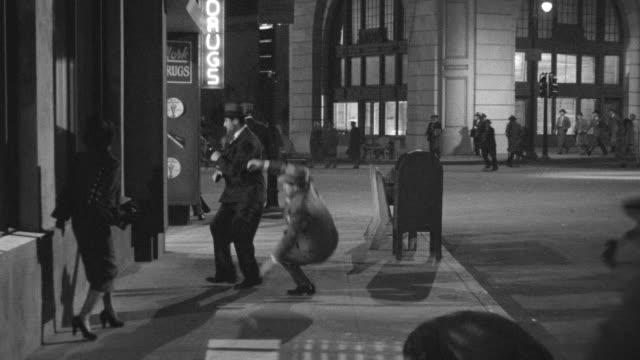 WS TS Shot of man firing on street pushing walking man and run away from car as police arrives