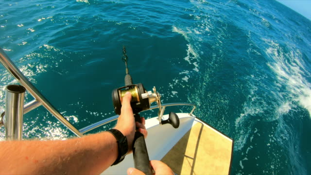 pov shot of man fishing in sea from moving boat on sunny day - great barrier reef, lizard island - 釣りをする点の映像素材/bロール