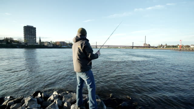 MS Shot of man fishing on the river Rhein / Duisburg, Germany