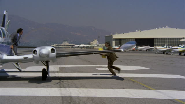 stockvideo's en b-roll-footage met ms ts shot of man going to airplane and starting plane at whitman airport - vliegveld