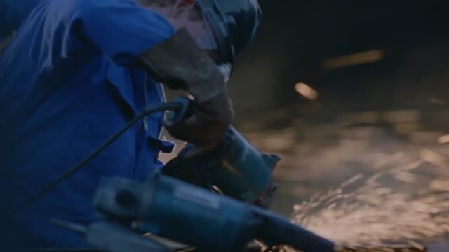 cu pan shot of man grinding metal - metal worker stock videos and b-roll footage