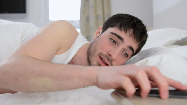 ms shot of man in bed checking mobile phone and smiling / london, greater london, united kingdom - greater london stock videos & royalty-free footage