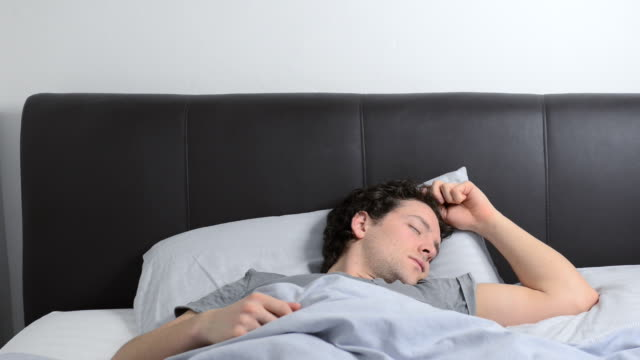 ms shot of man in bed waking up and getting out of bed / london, greater london, united kingdom - getting out stock videos and b-roll footage