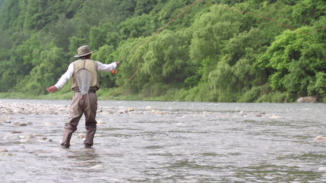 MS SLO MO Shot of man in fishing gear tossing out line into stream (fly fishing) / Jeongseon, Gangwon do, South Korea