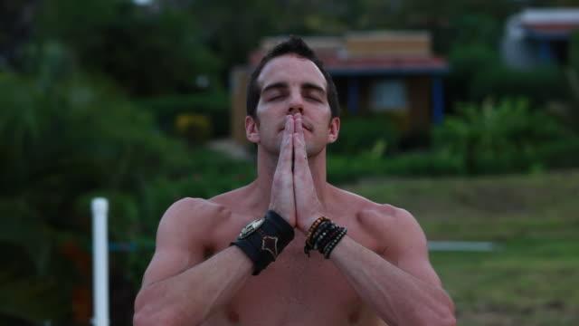 vídeos de stock, filmes e b-roll de cu shot of man in prayer pose smiling and meditating / montezuma, costa rica - kelly mason videos