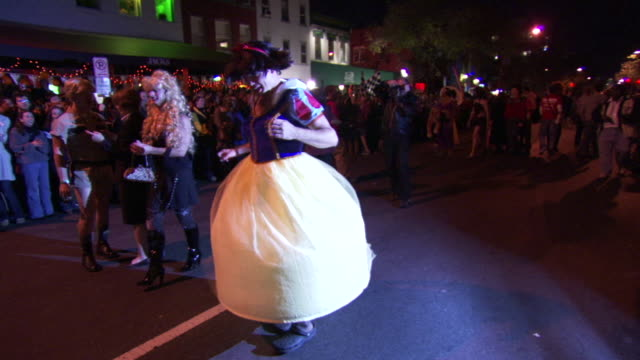 WS Shot of man in princess drag costume twirls and laughing during high heel race in DuPont Circle / Washington, Dist. of Columbia, United States
