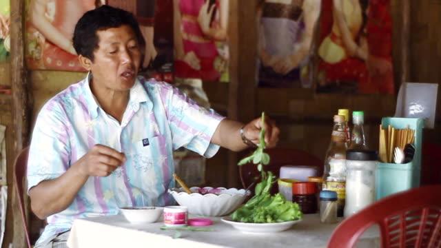 vidéos et rushes de ms slo mo shot of man in restaurant sitting at table and eating / nong khio, luang prabang, laos - un seul homme d'âge moyen