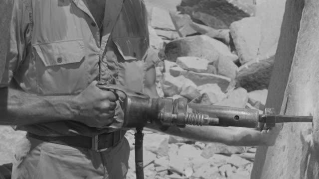 cu shot of man jackhammering large rock in quarry - einzelner mann über 30 stock-videos und b-roll-filmmaterial